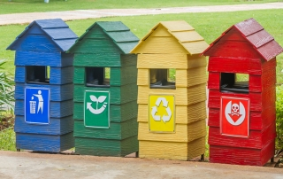 Blue, green, yellow and red bins on stand near footpath.
